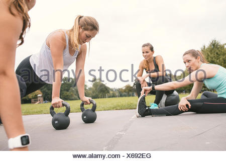 Four women having an outdoor boot camp workout - Stock Photo