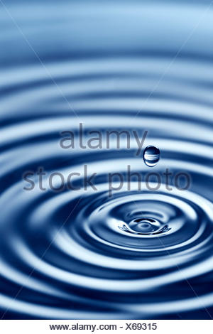 Water dripping into water causing a splash and ripples - Stock Photo