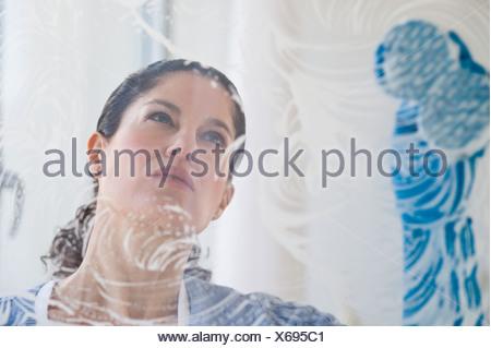 Hispanic woman washing window - Stock Photo