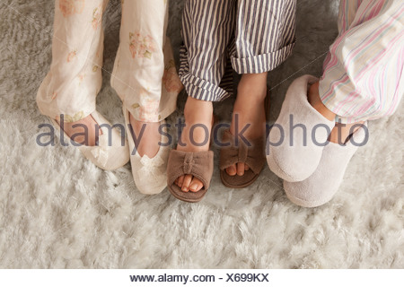 Close-up of three females in slippers - Stock Photo