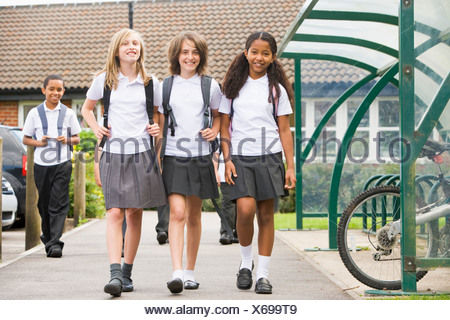 Three students leaving school with other students in background - Stock Photo