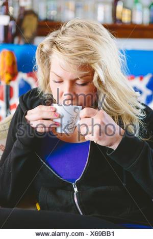 Greece, Dodecanese, Kalymnos, Blonde woman drinking coffee - Stock Photo