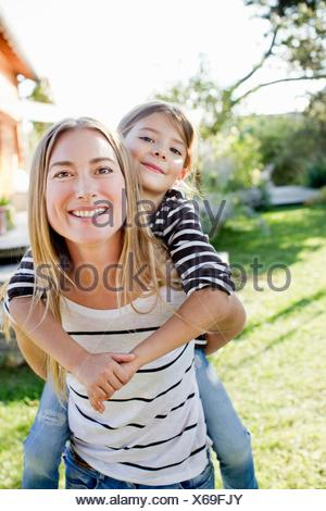 Mother giving daughter piggy back - Stock Photo
