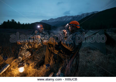 Male hunter friends in headlamps smoking pipes at campsite in remote field below mountains at night - Stock Photo