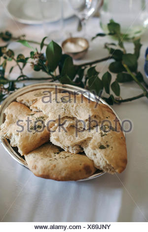 Freshly baked foccacia bread with rosemary in a bowl on a set up table - Stock Photo