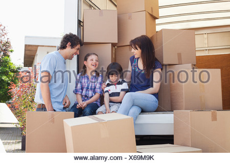 Family sitting on back of moving van - Stock Photo