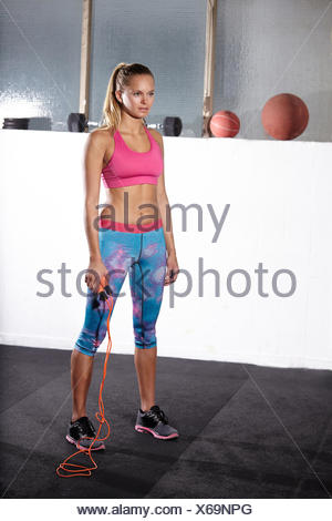 Portrait of young woman with skipping rope in gym - Stock Photo