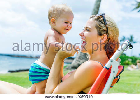 Woman sitting under palm tree with little son (18-23 months) - Stock Photo