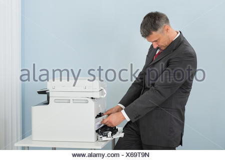 Businessman Removing Paper Stuck In Printer At Office - Stock Photo
