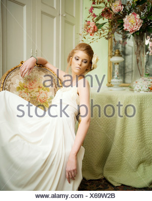 A young woman sitting on a chair, looking elegant - Stock Photo