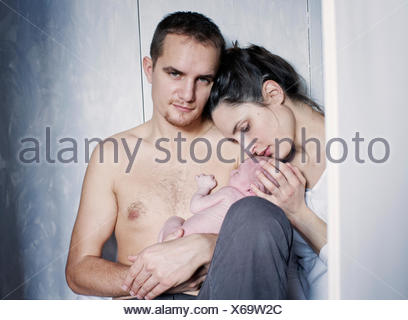 New parents sitting with newborn baby - Stock Photo