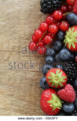 Frische Beeren wie Erdbeeren, Blaubeeren, Himbeeren, Johannisbeeren und Brombeeren auf einem Holzbrett - Stock Photo