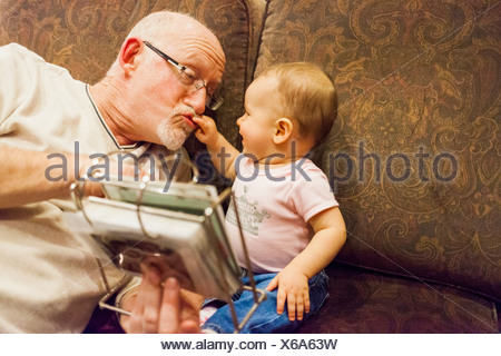 Grandfather playing with baby granddaughter - Stock Photo