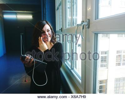 Happy Young Businesswoman With Laptop In Office Corridor - Stock Photo
