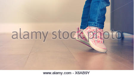 Baby girl learning to stand on her feet - Stock Photo