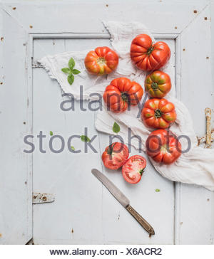 Fresh ripe hairloom tomatoes in rustuc blue wooden tray, top view, copy space - Stock Photo