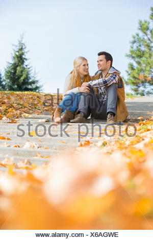 Happy young couple sitting on steps in park - Stock Photo
