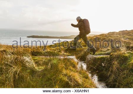 A man with a rucksack and winter clothing leaping across a small stream in an open exposed landscape. - Stock Photo