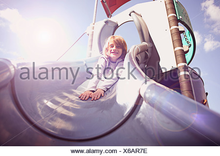 Boy coming down slide on front - Stock Photo