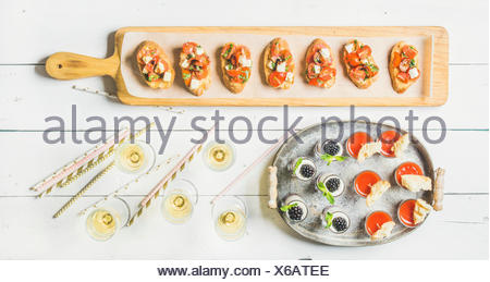 Brushetta sandwiches with tomatoes, gazpacho shots, desserts with berries and champagne in glasses, straws on corporate event, christmas, birthday, we - Stock Photo