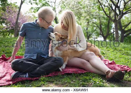 Young couple with corgi dog sitting in park - Stock Photo