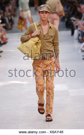 Burberry Milan Menswear S S Checked baker boy cap, olive cardigan and flower print trousers with big holdall bag - Stock Photo