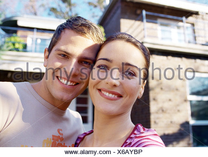 Couple in front of house, smiling, portrait - Stock Photo