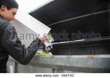 Teenage boy emptying bin with paper waste to recycling bin - Stock Photo