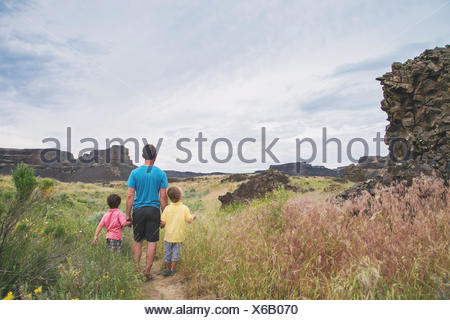 Rear view of father walking with two sons - Stock Photo