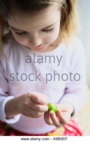 Liitle girl unpacking Easter egg, close-up - Stock Photo