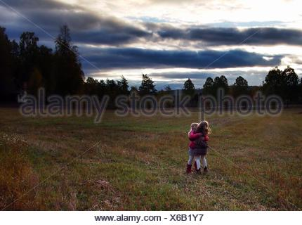 Sweden, Two girls (6-7 years, 8-9 years) hugging outdoors - Stock Photo