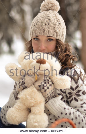 Beautiful, nice, smiling,little and wearing sweater hut and mittens and little girl with a teddy bear in winter forest.Portrait of lovely girl with cute,nice toy.Cute,beautiful,nice girl hug a fluffy,white,beige teddy bear.Girl and bear in winter - Stock Photo