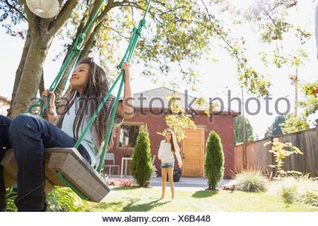 Girl on tree swing in sunny backyard - Stock Photo