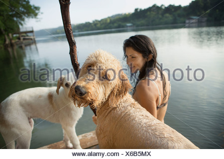 A woman swimming with her two dogs in a lake. - Stock Photo