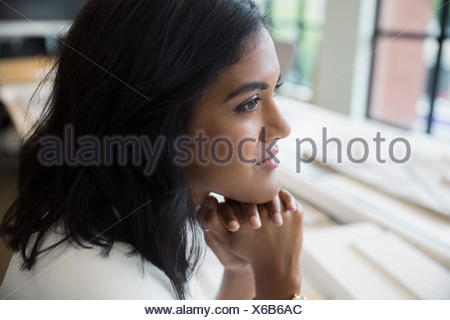 Close up pensive female architect looking away - Stock Photo