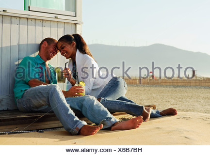 Couple sitting on the beach - Stock Photo