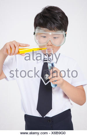 Elementary school boy wearing experimental goggles and holding test tubes - Stock Photo