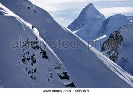 Freeskier downhill skiing in deep snow, Chandolin, Canton of Valais, Switzerland - Stock Photo