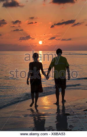 couple walking barefooted along the beach at sunset - Stock Photo