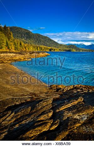 Sunlit rocks line the blue waters of Settler's Cove,  Settler's Cove State Recreation Site, Ketchikan, Southeast Alaska, Summer - Stock Photo