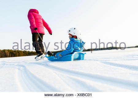 Sweden, Sodermanland, Jarna, Mother with son (2-3) tobogganing - Stock Photo