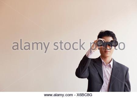 Businessman looking through a pair of binoculars - Stock Photo