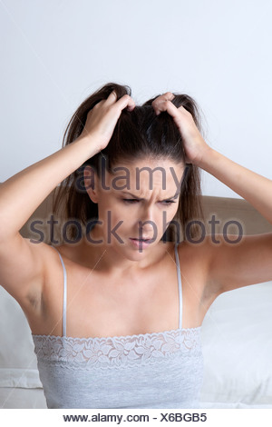 Woman scratching her head in bed - Stock Photo