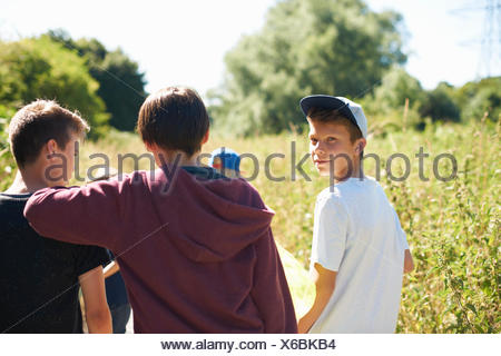 Portrait of boy wearing cap with friends - Stock Photo
