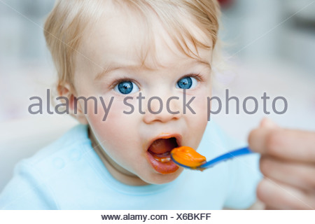 baby being fed looking at viewer - Stock Photo