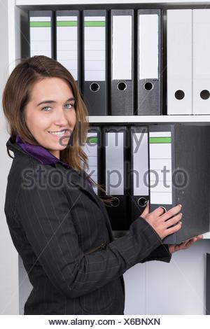 Eine junge, lächelnde Frau nimmt einen Aktenordner aus einem Regal im Büro. Die Frau schaut dabei zur Kamera. - Stock Photo