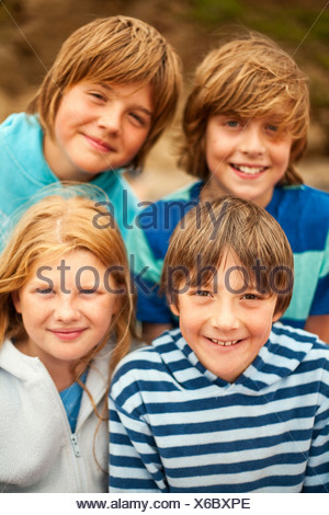 Portrait of four friends smiling at camera - Stock Photo