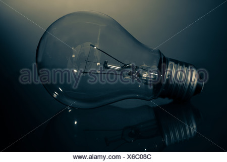 Clear light bulb lay on its side in darkness - Stock Photo