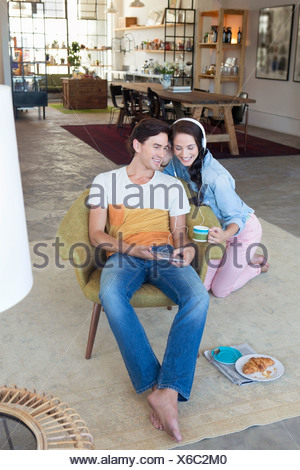 Smiling couple listening to music on headphones with digital tablet in livingroom - Stock Photo