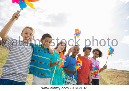Portrait of children holding pinwheels in field - Stock Photo